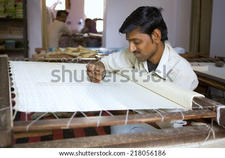 VARANASI, INDIA, DEC 9, 2013: Unidentified man embroidering a traditional sari cloth, on old fabric factory on Dec 9, 2013, Varanasi, India. Textile industry in Varanasi preserved ancient traditions - stock photo
