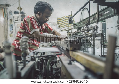 VARANASI, INDIA - 21 FEBRUARY 2015: Worker repairs textile machine in small factory. Post-processed with grain, texture and colour effect. - stock photo
