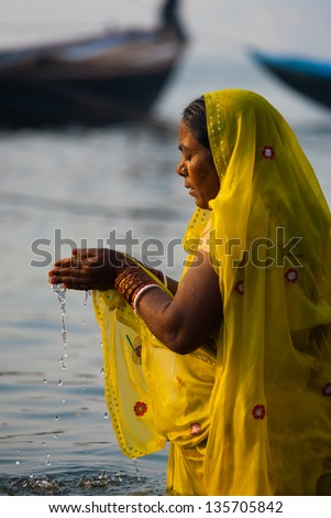 VARANASI, INDIA - JANUARY 29: A devout hindu woman cups water in her hands in prayer and bathes, an important cultural tradition, in the holy Ganges river on January 29, 2008 in Varanasi, India - stock photo