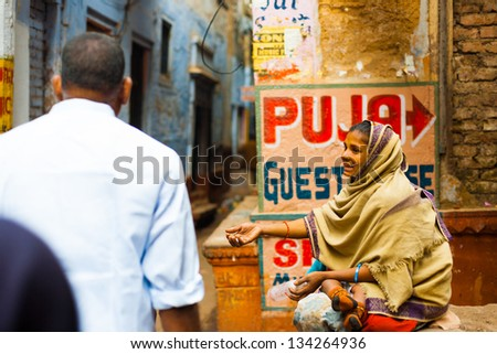VARANASI, INDIA - JANUARY 31, 2008: An unidentified poor beggar with baby extends her hand to beg for money in the holy city of Varanasi, India on January 31, 2008. Poverty is a major issue in India - stock photo