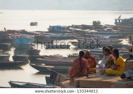 VARANASI, INDIA - JANUARY 28, 2008: An unidentified priest blesses the surviving members of a family on a ghat along the Ganges river following hindu custom on January 28, 2008 in Varanasi, India - stock photo
