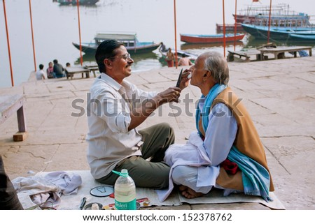 VARANASI, INDIA - JANUARY 1: Hairdresser cuts client mustache with huge scissors on the banks of the river Ganges on January 1, 2013. Varanasi urban agglomeration had a population of 1,435,113.