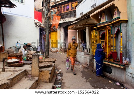 VARANASI, INDIA - JANUARY 2: Traditional street life with a sellers, a praying woman and passers-by people at morning on January 2, 2013. Varanasi urban agglomeration had a population of 1,435,113  - stock photo