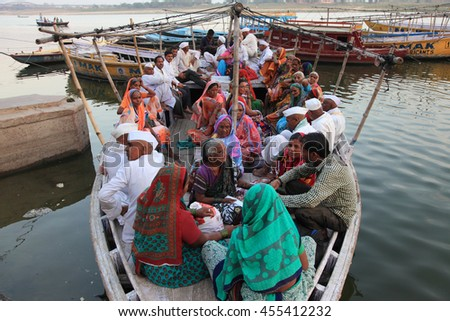 VARANASI, INDIA- MAR 11:Unidentified pilgrims sit on a boat to cross the holy river Ganges on March 11, 2016 in Varanasi, Uttar Pradesh, India.Varanasi is the most popular pilgrim place in India. - stock photo