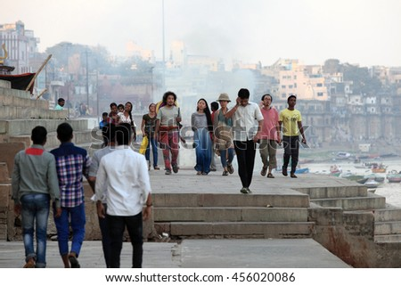 VARANASI, INDIA- MAR 03:Unidentified tourists walk on the banks of the river Ganges on March 03, 2016 in Varanasi, Uttar Pradesh, India.Varanasi is the most popular pilgrim place in India. - stock photo