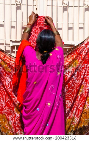 VARANASI, INDIA - MAR 2, 2013: Woman hanging sari for drying on the banks of Ganges river, Varanasi, India