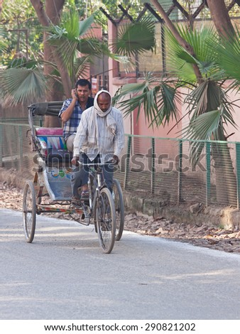 VARANASI, INDIA - MARCH 4, 2015: A cycle rickshaw transports a passenger in the centre of the city. This type of vehicle is extensively used by people to get around congested Indian cities