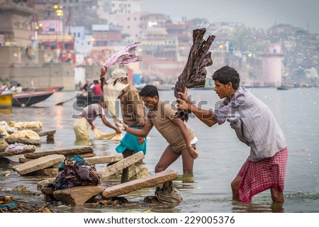 VARANASI, INDIA - MARCH 21, 2013: A washer is working in the holy water of the river Ganges, in Varanasi - stock photo