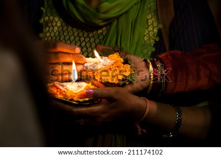 Varanasi, India - March 03, 2013: Woman lighting candles during Ganga Aarti ceremony on the ghats of Ganges river during Kumbh Mela festival - stock photo