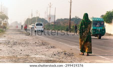 Varanasi, India - November 23, 2014: Indian woman walking on the road in indian traditional dress sari.  - stock photo