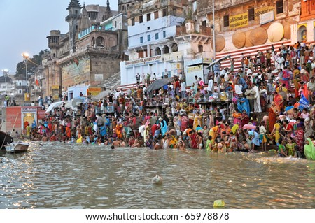 VARANASI, INDIA - 29 OCTOBER: An unidentified group of Indian people wash themselves in the river Ganga on October 29, 2009.  The holy ritual of washing is held every day. - stock photo