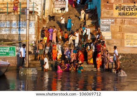 VARANASI, INDIA - SEPTEMBER 9 - Indian people on the steps of Manasarowar ghat wash themselves in the river Ganges on September 9, 2011 in Varanasi, India. They do this rite every day. - stock photo