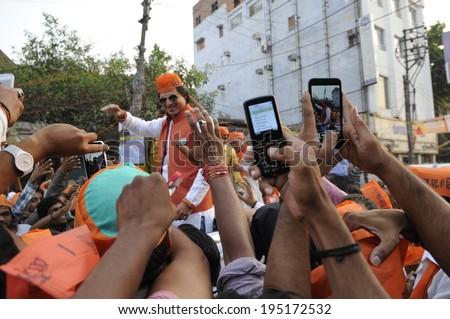 VARANASI - MAY 6: People photographing bollywood actor Vivek Oberoi while   campaigning for Narendra Modi during a road show on May 6, 2014 in Varanasi , India. - stock photo