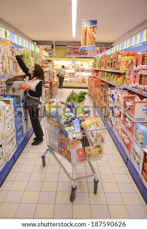 VARESE, ITALY-APRIL 11, 2014: A woman shopping next by a full shopping cart in a supermarket aisle, in Varese.