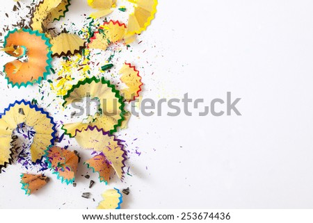 varicolored pencil shavings on white background with copy space - stock photo