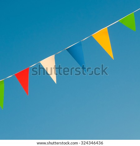 Varicolored pennants on a rope against clear blue sky; Bunting flags; Let's have a party - stock photo
