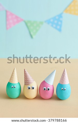 Variegated eggs in festive caps on pastel background. Interesting Easter idea. Festive garland . Colored eggs with eyes. The decoration on the day of birth.