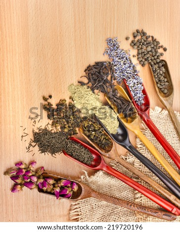 variety assortment of dry tea in scoops on wooden table background, top view - stock photo
