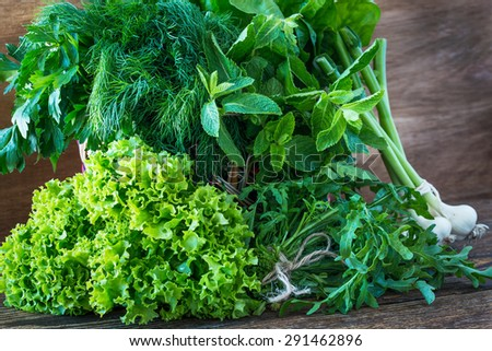 Variety fresh organic herbs on wooden background, parsley, dill, mint, spinach, garlic, arugula,  lettuce. Rustic style - stock photo
