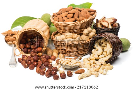Variety  nuts  (shelled and in their shells)  including almonds, cashew, hazelnuts, brazil nuts, peanuts, green walnuts with leaves and pine nuts.  Isolated on white background  - stock photo