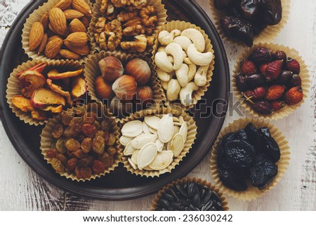 Variety of 7 assorted nuts and dried fruits, top view - stock photo