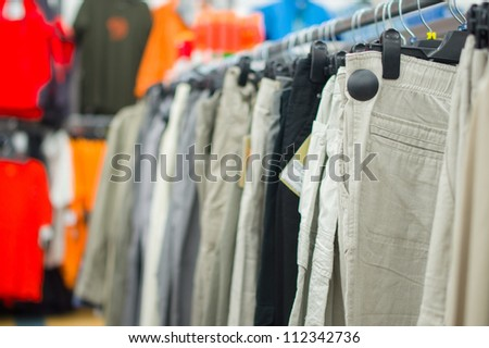 Variety of bright and dark trousers on stands in supermarket - stock photo