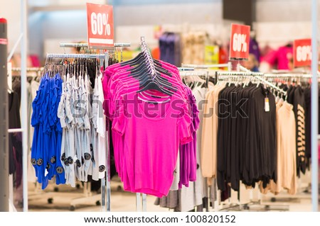 Variety of bright cardigans on stands in mall - stock photo