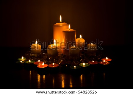 Variety of candles lights with reflection on a wood table in darkness