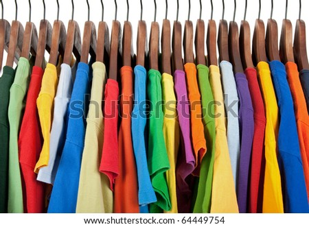 Variety of casual clothes of different colors on wooden hangers. - stock photo