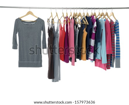 Variety of casual female clothes of different colors on wooden hangers
