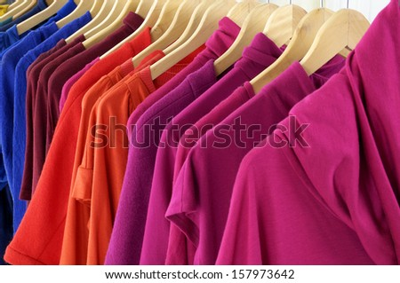 Variety of casual female clothes of different colors on wooden hangers - stock photo
