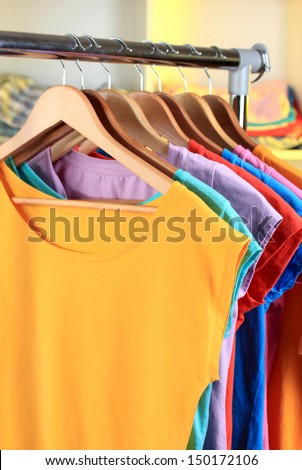 Variety of casual t-shirts on wooden hangers on shelves background