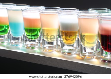 Variety of colorful green blue yellow red and white beautiful alcohol sweet shooters shots cocktail fresh beverage in small glasses standing in row on bar studio closeup, horizontal picture - stock photo