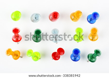 variety of colorful pushpins pinned on white paper - stock photo