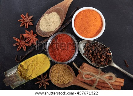 Variety of colorful spices, black background - stock photo