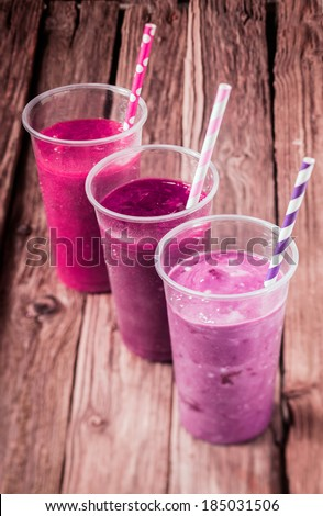 Variety of delicious berry smoothies with strawberry and blueberry blended with low fat yogurt for a healthy summer drink, high angle view standing in a diagonal row - stock photo