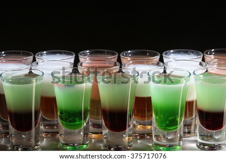 Variety of different multicolored green red white tasty alcohol shots liquid in transparent beautiful drinking glasses standing in line on black background closeup studio, horizontal picture - stock photo