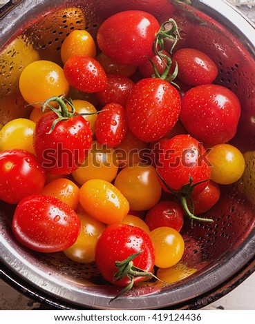 Variety of different tomatoes: red, orange, yellow and cherry freshly washed in colander - stock photo