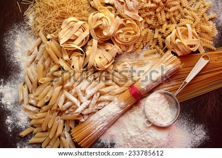 Variety of dry italian pasta on wooden board - stock photo