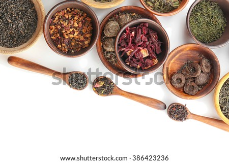 Variety of dry tea in pots and wooden spoons isolated on white, copy space