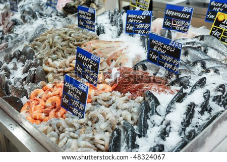 Variety of fish and seafood on cooled market display, TMs removed from tags - stock photo