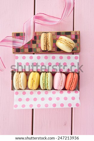 Variety of french macarons on pink wooden boards - stock photo