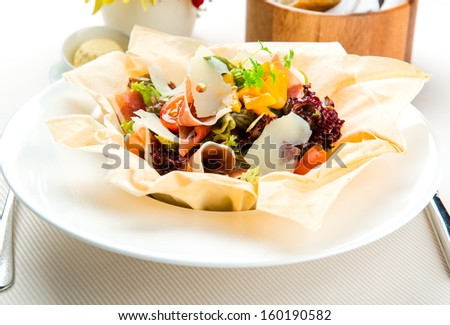 Variety of fresh leaf salad with Parma ham, asparagus and mango dressing served in filo pastry basket  - stock photo