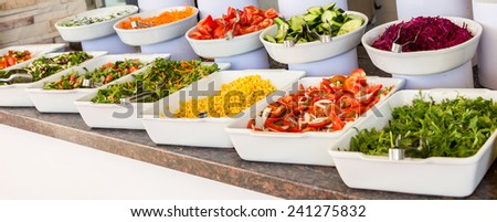 Variety of fresh salads in a buffet - stock photo