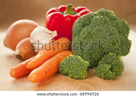 Variety of fresh vegatables on wooden board. - stock photo