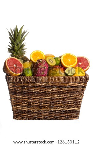 Variety of fruits in wicker basket over plain white background.