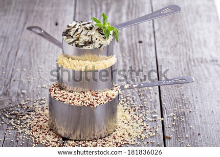 Variety of grains in stacked measuring cups - stock photo