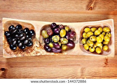Variety of green, black and mixed marinated olives in olive tree dish on wooden table. Above point of view - stock photo