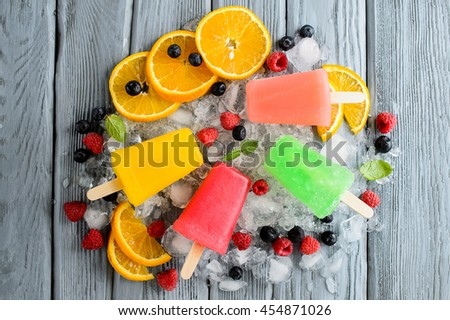 Variety of healthy ice popsicles with fruits and berries on ice, top view - stock photo