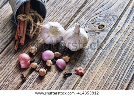 Variety of herb and spices on wooden background. Shallot, Cardamom, Cinnamon sticks, Fresh garlic. Healthy ingredients, Cuisine ingredients. - stock photo
